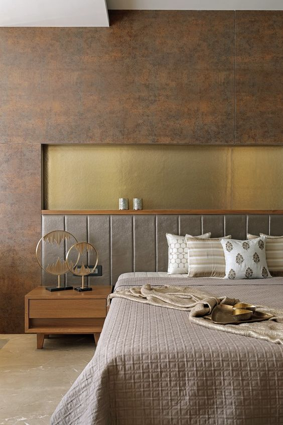 a luxurious bedroom in earthy tones, with a rust metal accent wall, an upholstered grey bed, a gold insert and elegant bedding