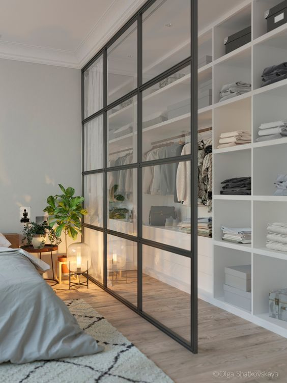a modern bedroom and a closet separated with a French window divider looks airy and chic and features storage space here