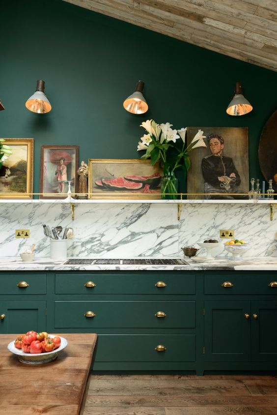 a vintage hunter green kitchen with a white marble backsplash and countertops, a shelf with artworks is chic