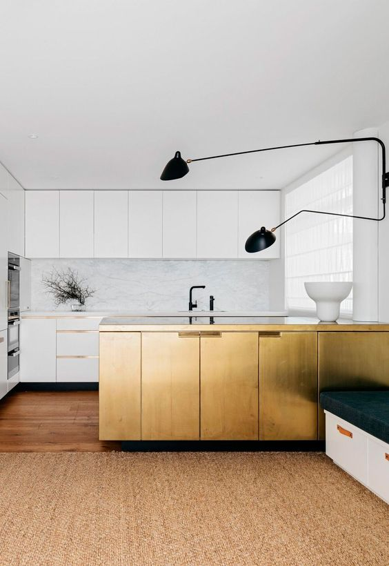 a white minimalist kitchen with a white stone backsplash and countertops, black fixtures and a gilded kitchen island for a statement
