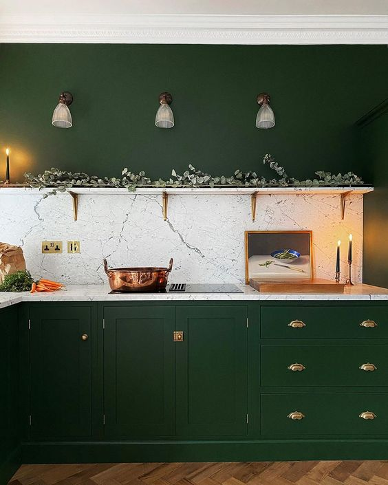a hunter green kitchen with vintage cabinets, gold handles, an open shelf with greenery and a white stone backsplash
