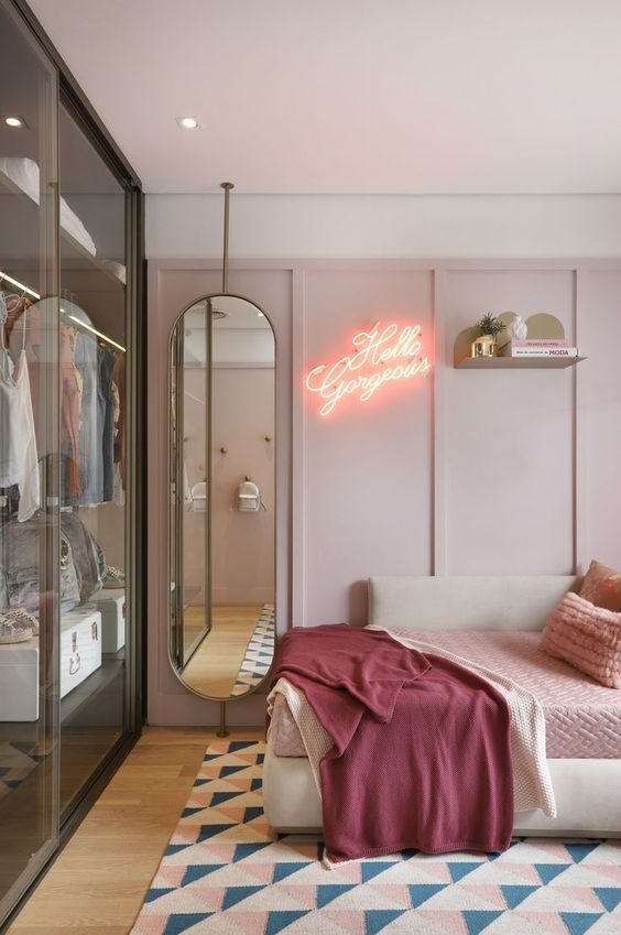 a modern and fashionable girlish bedroom in pink, with elegant furniture and a glass closet with sliding doors