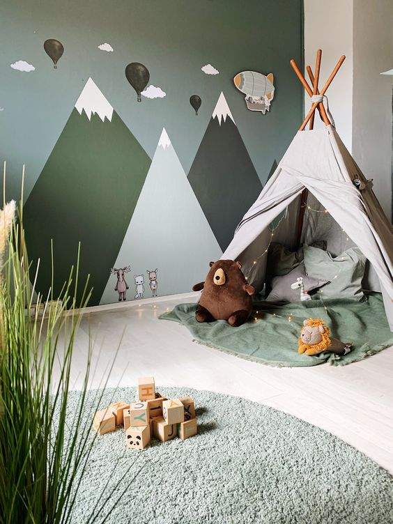 a pretty adventurous nursery with a mountain wall mural, a teepee with lights, green textiles