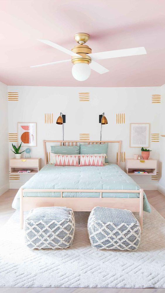 a pretty bedroom with a pink ceiling, light-stained furniture, an accent wall, mint bedding and ottomans in blue and white