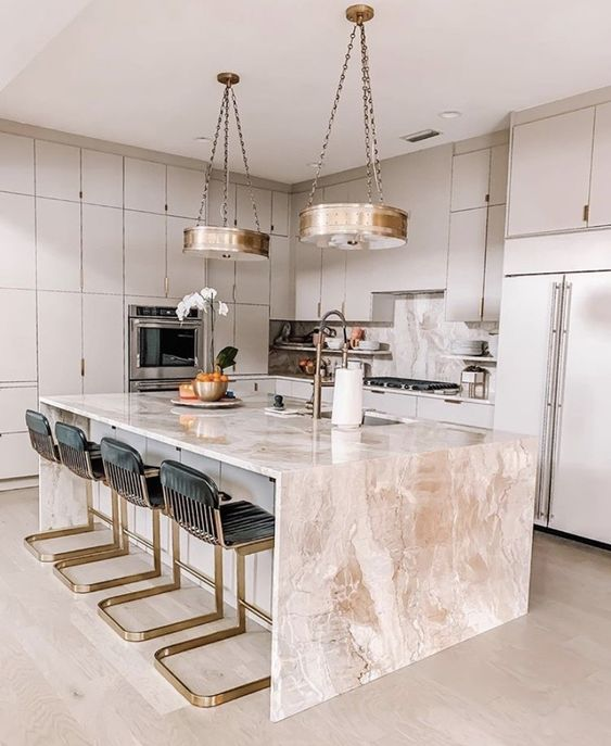 an elegant dove grey kitchen with a pink stone kitchen island, whimsy black and gold stools and gold pendant lamps