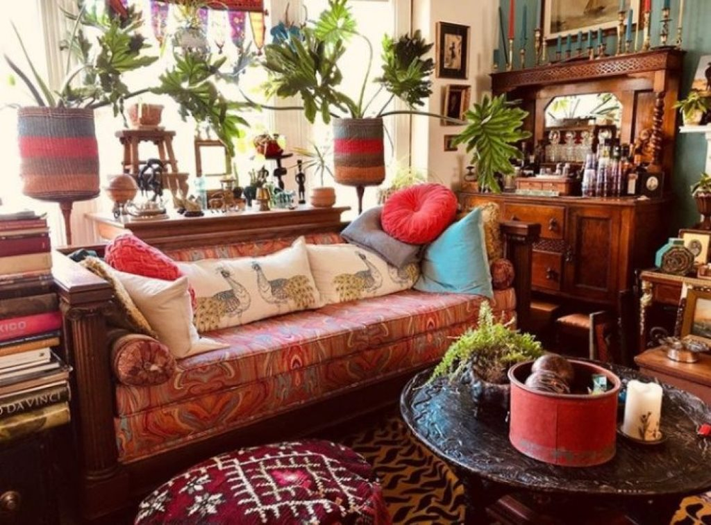 a bright maximalist living room with heavy vintage furniture, colorful textiles, colorful pillows and potted plants