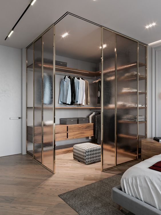a masculine bedroom with a corner closet enclosed in frosty glass is a stylish and very modern idea to rock
