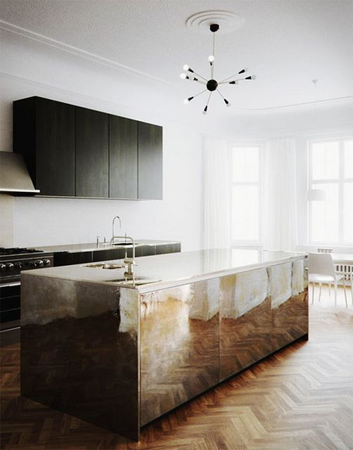 a minimal black kitchen with a shiny metal kitchen island that brings a glam feel to the space and make it stand out a lot