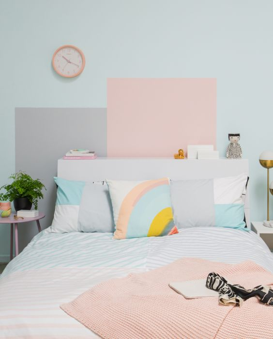 a pastel bedroom with a light blue wall and color blocking, pastel and color block bedding and a pink clock