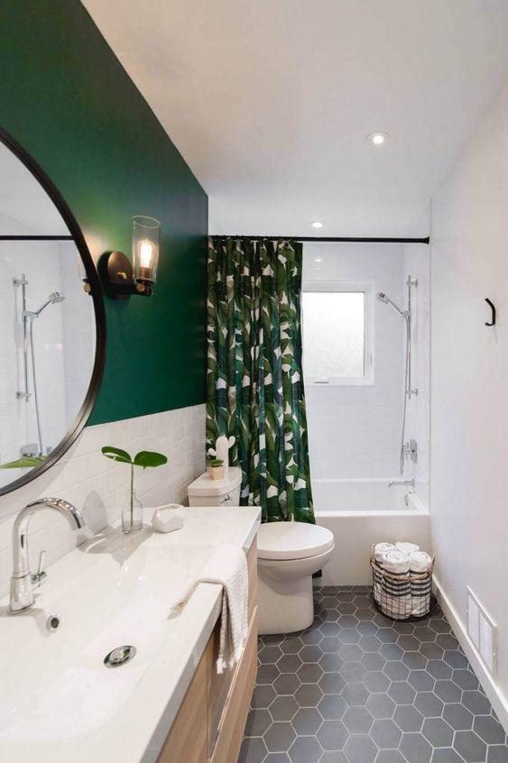 a stylish small bathroom with a green and white tile wall, a grey hex tile floor, white appliances and a tropical print curtain