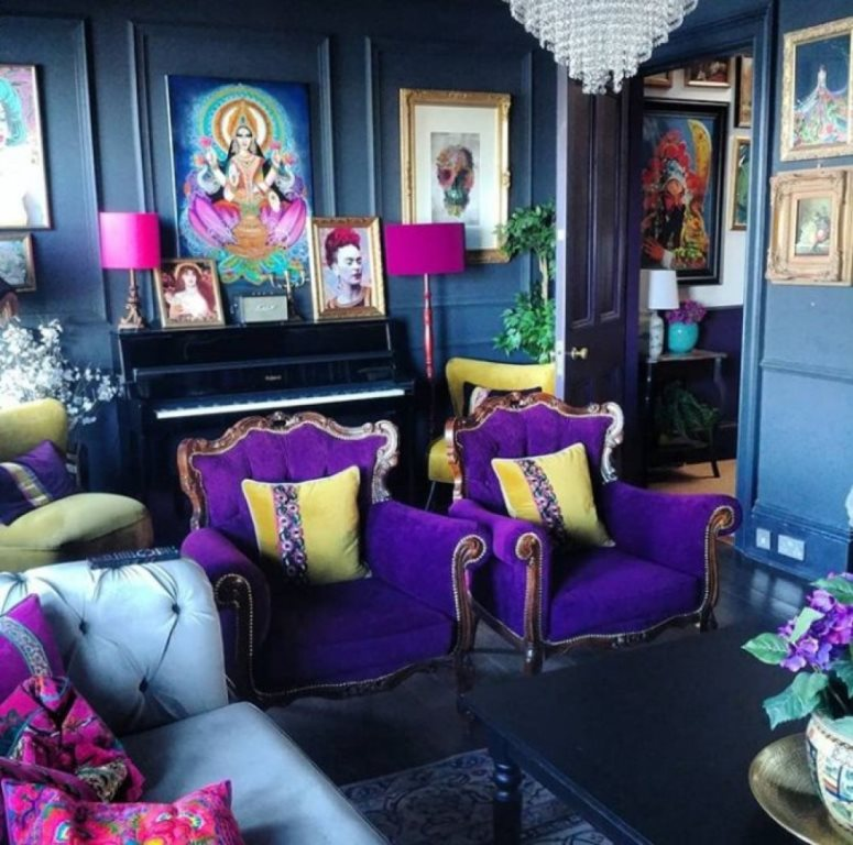 a bold maximalist living room with blue walls, pink and purple furniture, colorful artworks and potted plants