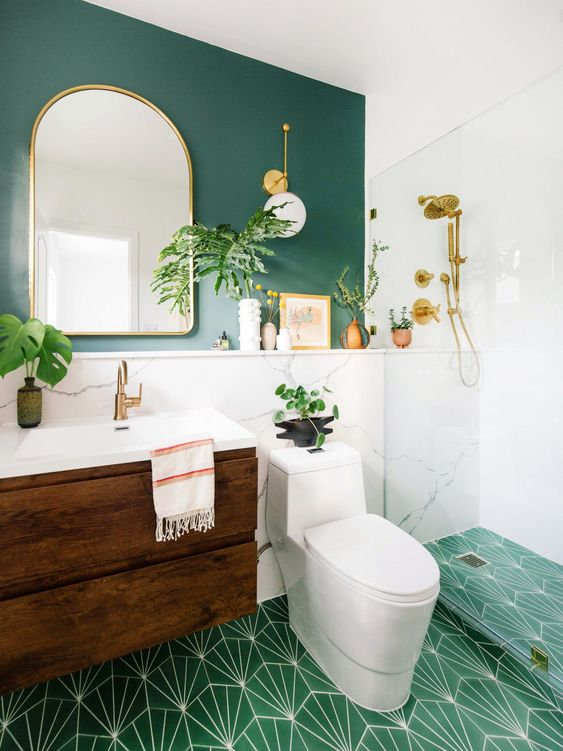 a chic modern bathroom with a green wall, white marble, a green printed tile floor, a floating wooden vanity