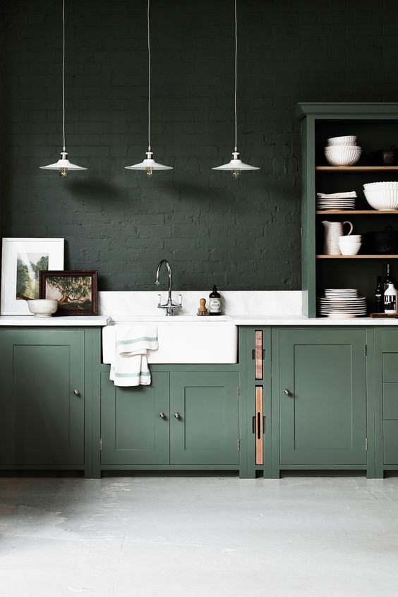 a moody hunter green kitchen with vintage cabinets, dark green brick walls, a white stone backsplash and countertops