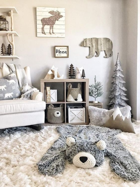 a neutral woodland nursery with wooden decorations and a faux bear skin plus animal-shaped baskets