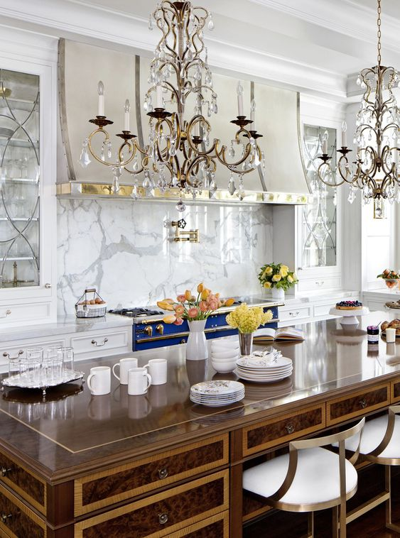 a refined vintage inspired kitchen in white, with a bold blue cooker, a white marble backsplash, crystal chandeliers and a vintage desk as a kitchen island