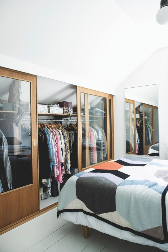a small attic bedroom in neutrals, with its awkward part covered with sliding glass doors and used as a closet