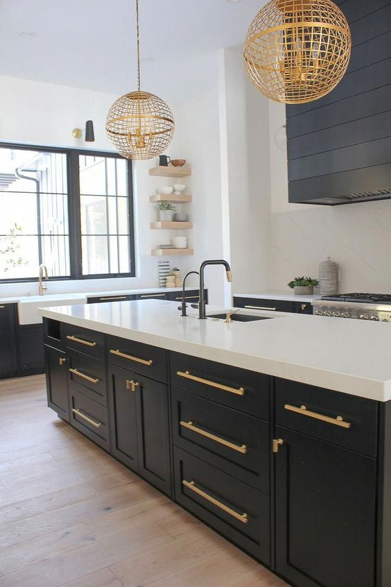 a contrasting graphite grey and white kitchen with gold handles and matching gold globe pendant lamps looks chic