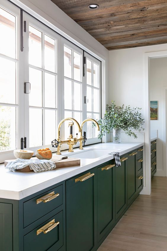 a hunter green modern kitchen with white stone countertops, gold handles and fixtures and a window instead of a backsplash