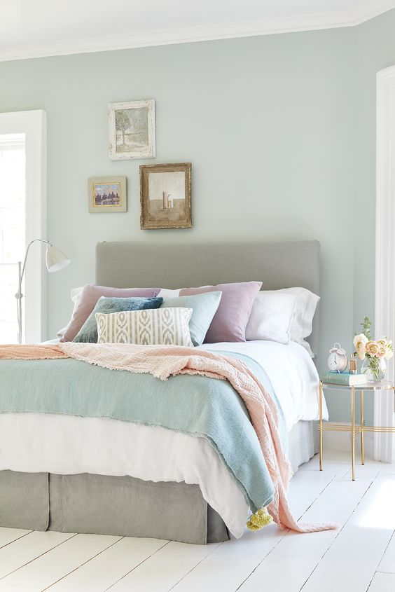 a light blue bedroom with a grey bed, pastel bedding, blooms and a small vintage gallery wall