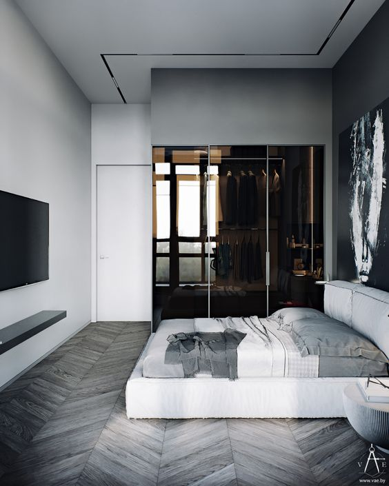 a minimalist master bedroom with a part of it taken by a closet in brown glass is very chic and refined