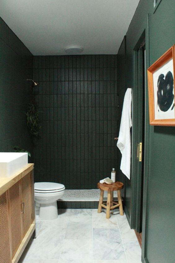 a refined and moody dark green and black bathroom with a white marble tile floor and a wooden vanity