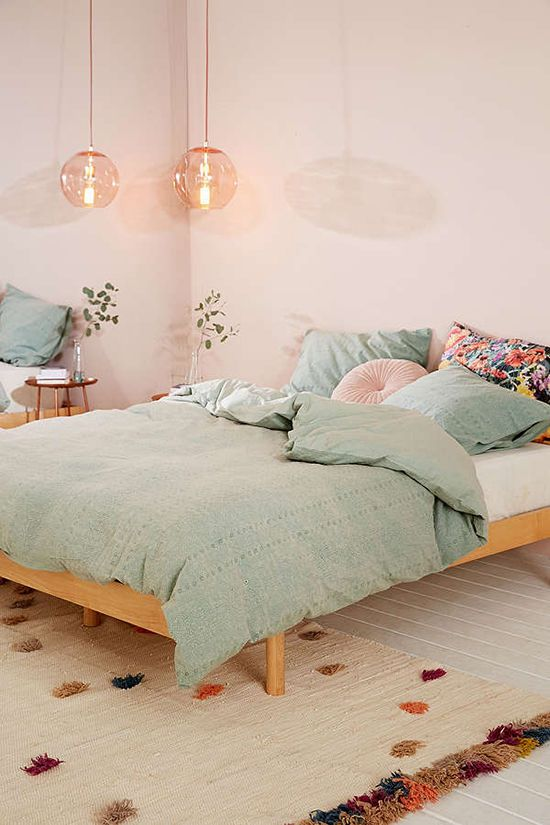 a blush bedroom with wooden furniture, mint-colored and pink bedding, pink pendant lamps and a bold rug