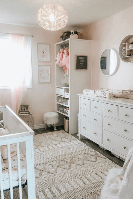 a cozy hygge nursery with blush walls, white furniture, an open wardrobe and a beautiful woven rug