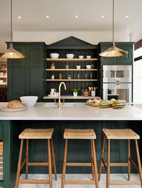 a sophisticated hunter green kitchen with vintage cabinets, open shelves, white countertops, metal pendant lamps and wooden stools