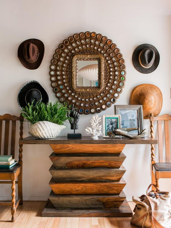 a catchy entryway with a wooden geometric console table, cowboy hats, potted greenery, driftwood and corals