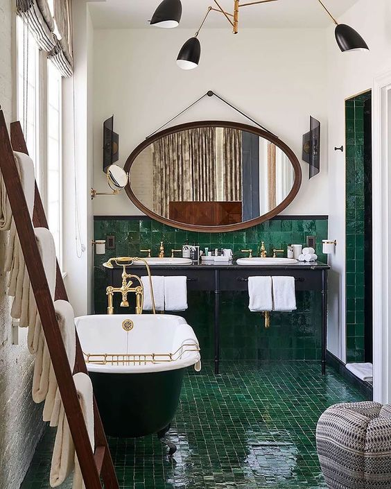 a fantastic 20s bathroom with green glossy tiles, a clawfoot tub, an oval mirror and a shared vanity is very beautiful