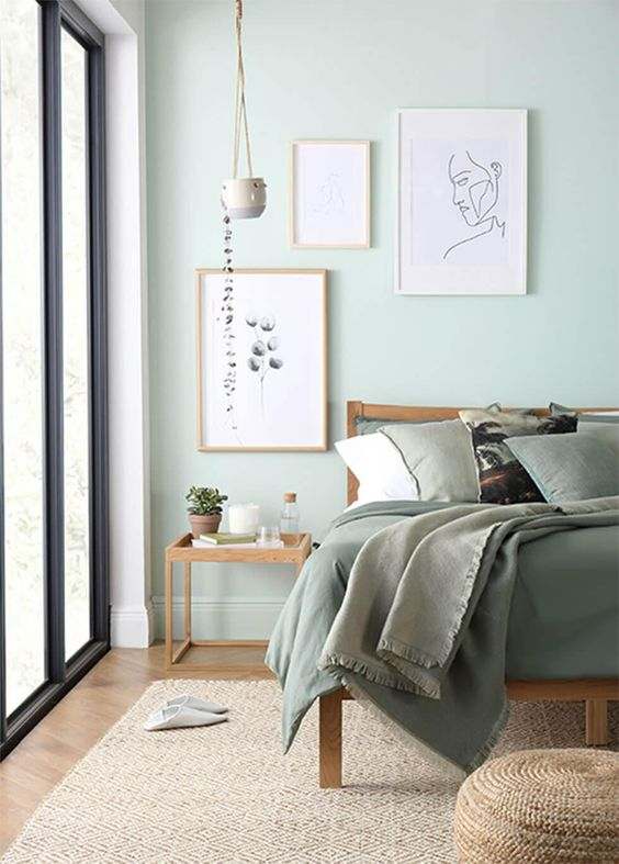 a pastel green bedroom with light stained wooden furniture, green bedding and a jute rug plus some plants