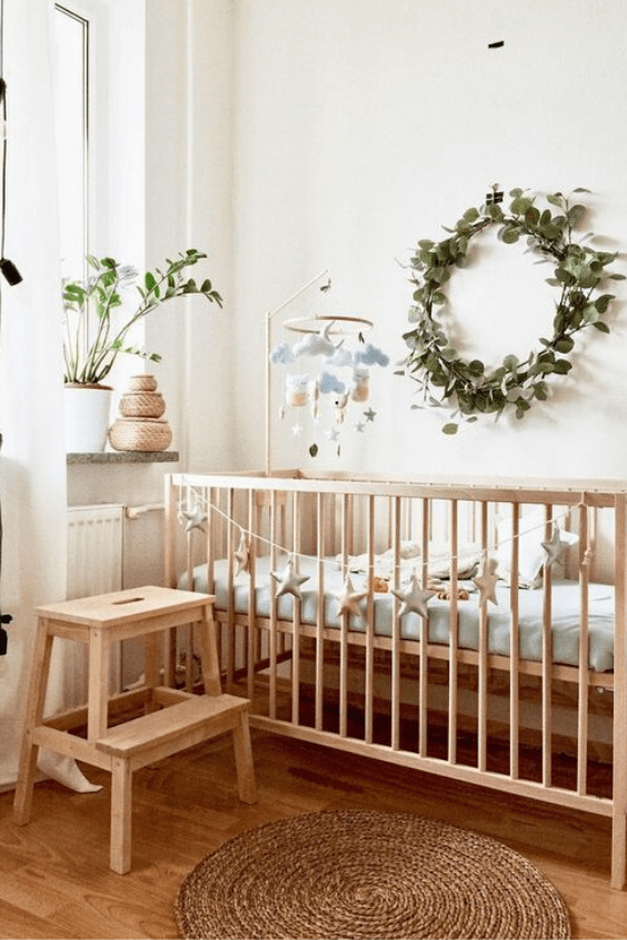 a pretty and welcoming neutral nursery with light stained wooden furniture, pastel bedding and a greenery wreath