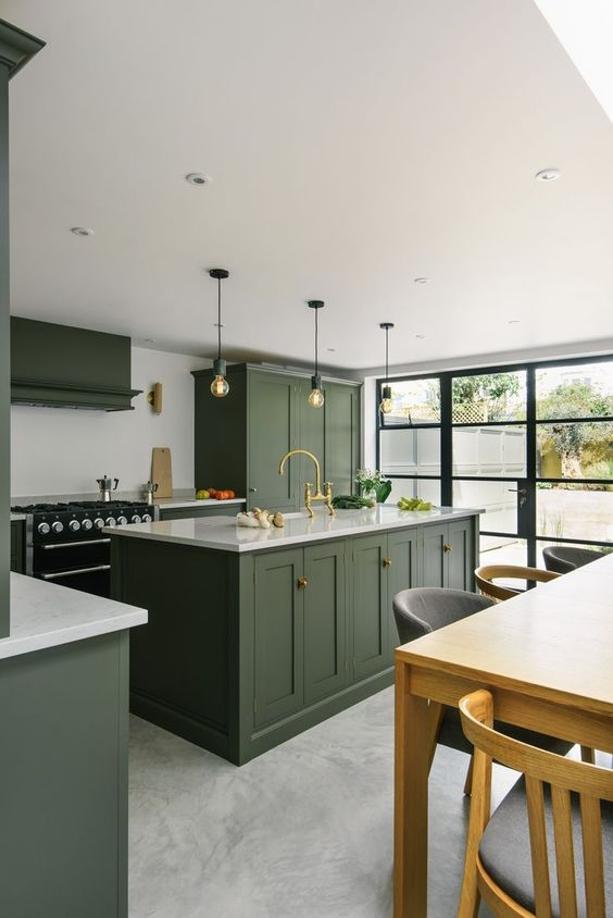 a stylish hunter green kitchen with vintage cabinetry, a white backsplash and countertops, pendant bulbs and a glazed wall
