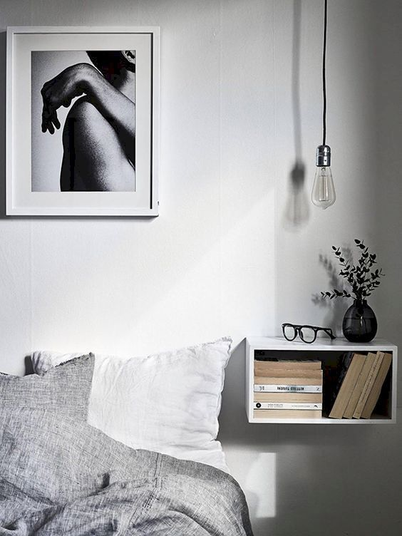 a Scandinavian bedroom with a floating open box nightstand with books and a bulb over the space