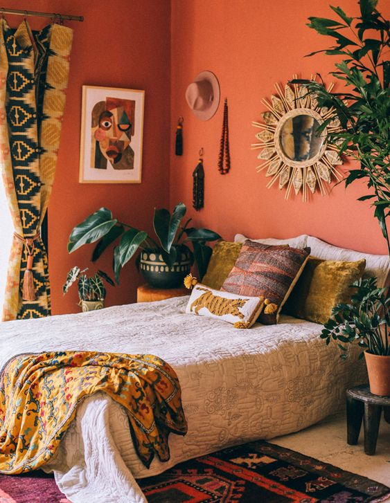 a colorful global style bedroom with red wlals, bright bedding, potted greenery and statement plants and printed textiles