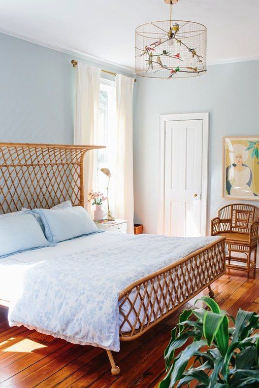 a light blue bedroom, rattan furniture, a catchy chandelier with birds, artworks and potted plants