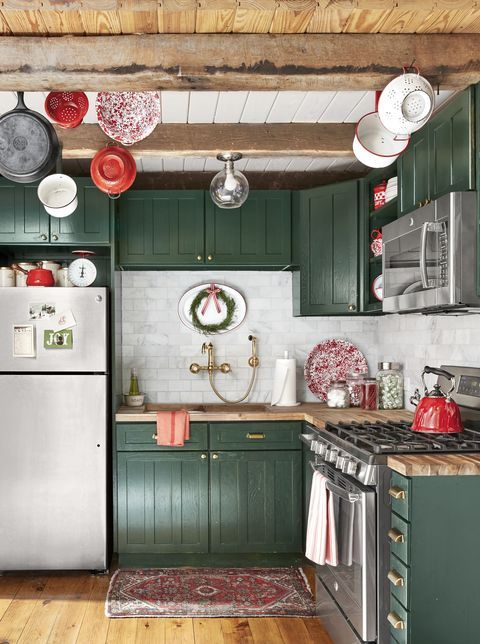 a pretty hunter green kitchen with butcherblock countertops and a white marble tile backsplash plus wooden beams on the ceiling