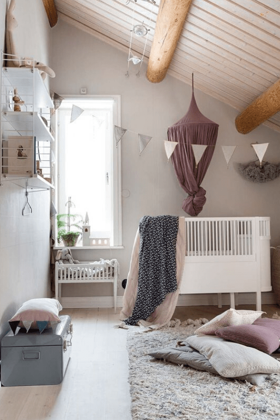 an attic neutral and pastel hygge nursery with modern furniture, pastel textiles and some prints is very welcoming