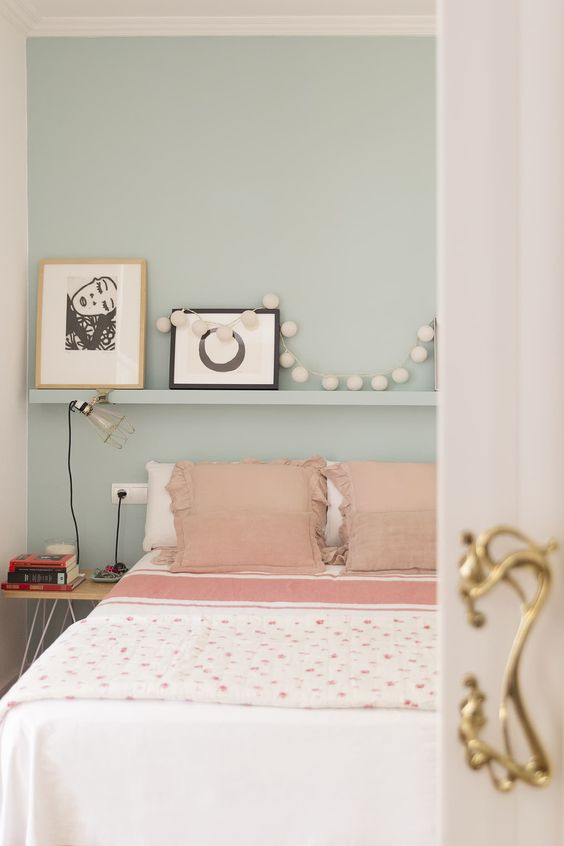 a light blue bedroom with a ledge, pink and white bedding, a garland and simple artworks is welcoming