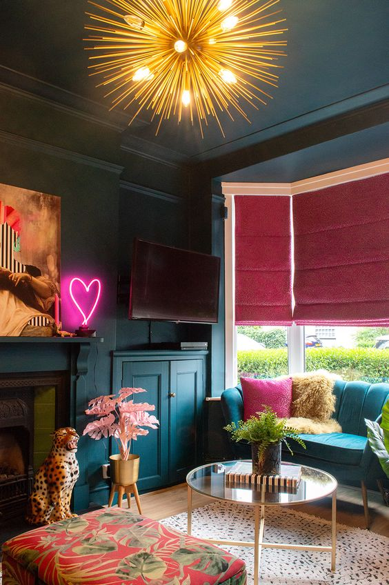 20 a moody maximalist living room with teal walls and furniture, a fireplace, pink and fuchsia touches and neon light
