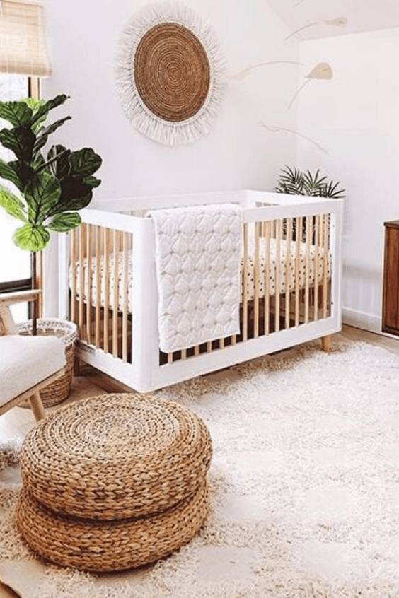 a neutral boho nursery with white furniture, jute ottomans, potted plants and a lovely jute decoration