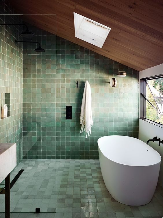 a very peaceful green tile bathroom with a wooden ceiling and a skylight, an oval tub and black fixtures
