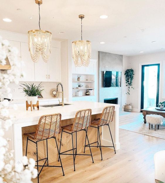 amazing wooden bead chandeliers, rattan stools make this white kitchen glam, chic and very outstanding
