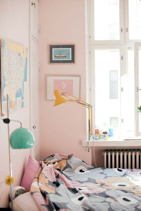 a bedroom with pink walls, artworks, floral bedding and colorful lamps is amazing for spring and summer