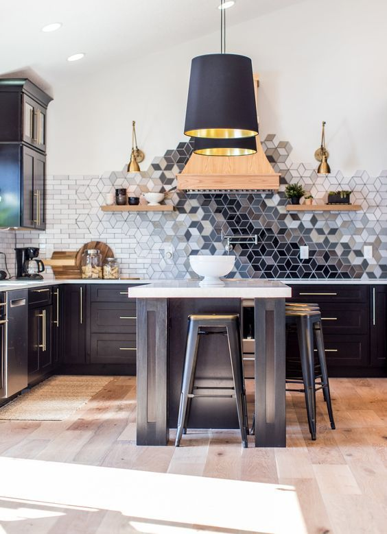 a black kitchen with a beautiful geometric ombre tile backsplash that is a whole masterpiece in here