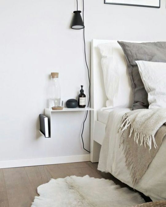a catchy minimalist nightstand in white, with a book stored and some stuff on top is very airy and cool