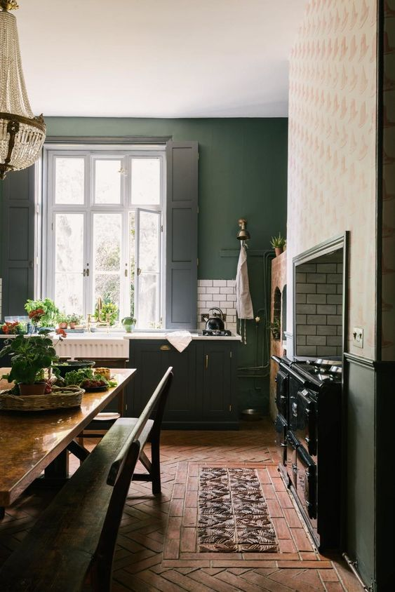 a vintage hunter green kitchen with a large vintage cooker, white countertops and black shutters and a dining space