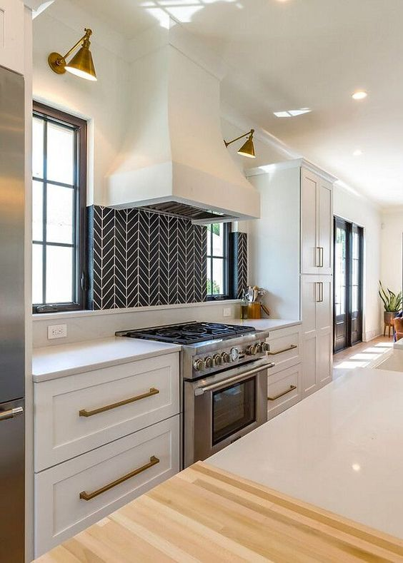 a chic white kitchen with brass handles, wall sconces and a statement black and white geometric tile backsplash