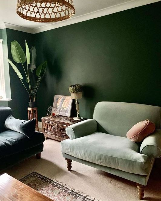 a green on green living room with dark walls, dark and light green furniture, potted plants and a beautiful carved chest