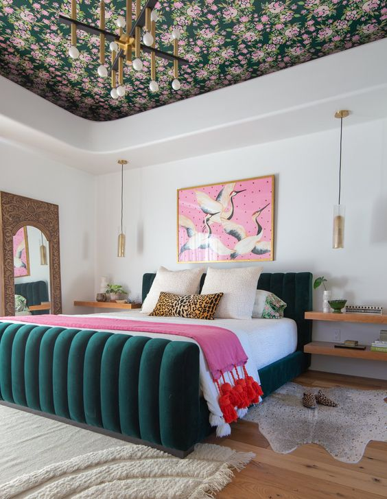 a refined and chic modern colorful bedroom with a floral ceiling, a hunter green bed and pink touches is cool